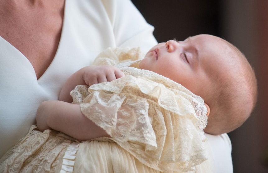 Un bébé en tenue de baptême