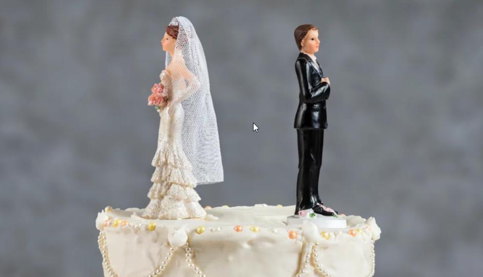 Une mariée en figurine tournant le dos au marié sur un gâteau de mariage